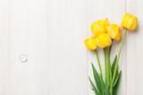 Fototapeta Tulipany - Yellow tulips on wooden table