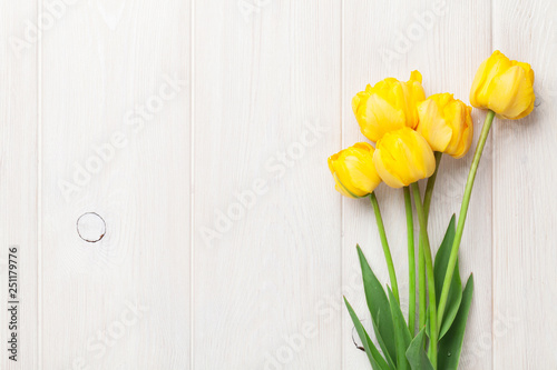Photo  Yellow tulips on wooden table