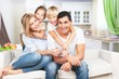Leinwanddruck Bild - Young  family at home smiling at camera