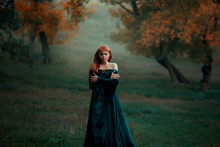 Lonely Sad Girl Walks Alone In Terrible Dark Dangerous Forest In Long Green Emerald Dress And Raincoat With Open Shoulders, Princess Got Lost And Froze, Young Witch With Red Hair Looks For Path Home