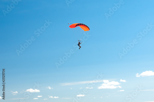 Stampa su Tela Parachutist soar on colorful parachutes across the boundless blue sky against the background of white fluffy clouds