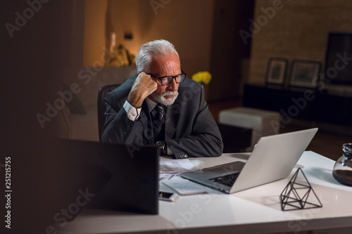 Fotografía  Focused senior businessman working late and reading an e-mail on laptop
