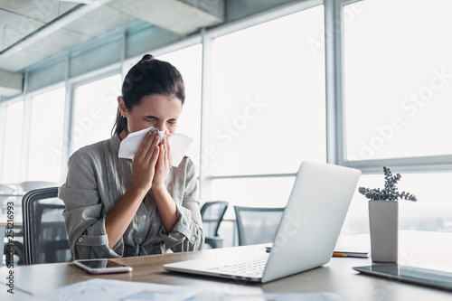 Sick and overworked businesswoman sitting at the desk in the office and blowing her nose, feeling unwell Fototapet