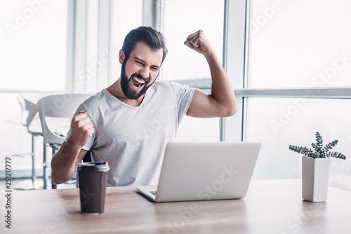Photo  Handsome dark-haired businessman celebrating success with arms raised while looking at his laptop screen