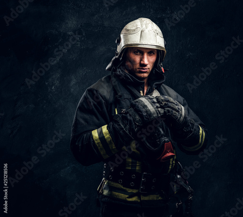 Firefighter in uniform and safety helmet posing in a dark studio, looking at the camera with a confident look Fototapete