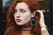 canvas print picture - Outdoor close up portrait of young beautiful redhead girl with natural long curly hair and feckled skin, wearing big blue plastic circle earrings, looking aside, posing in street