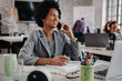 canvas print picture - Happy black businesswoman talking on mobile phone in the office.