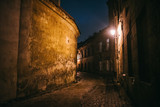Fototapeta Uliczki - Ancient narrow night Vilnius street with old architecture and winter background