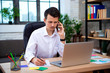 Successful businessman talking on phone using laptop sitting at office, young entrepreneur man speaking by cell and takes notes