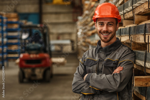 Fotografia  Shot of a bearded handsome metalworker in protective uniform and hardhat smiling joyfully to the camera posing at the warehouse