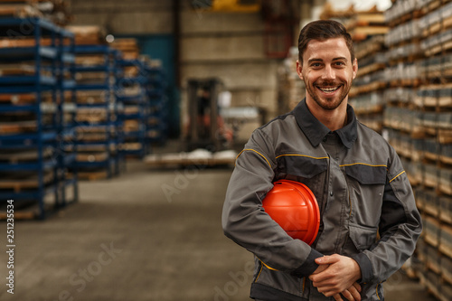 Pinturas sobre lienzo  Shot of a handsome young bearded factory worker in uniform holding protective ha