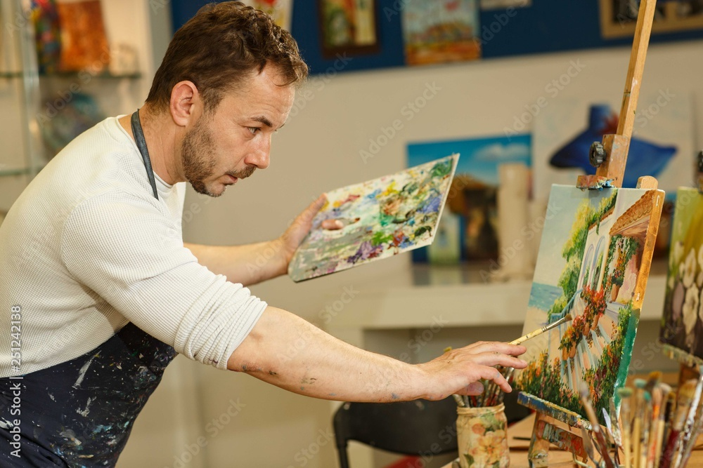Fototapety, obrazy: Side view of male artist with perfect imagination drawing picture by long brush, holding palette in hand. Creativity man with bread wearing uniform, working alone at workplace. Professional painter.