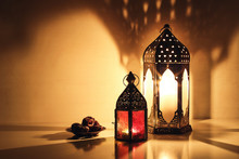 Ornamental Arabic Lanterns With Burning Candles Glowing At Night. Plate With Date Fruit On The Table. Festive Greeting Card, Invitation For Muslim Holy Month Ramadan Kareem. Iftar Dinner Background.