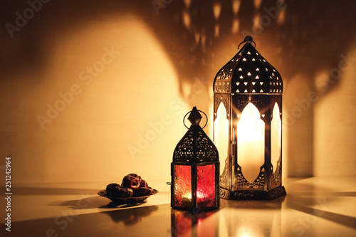 Fototapeta Ornamental Arabic Lanterns With Burning Candles Glowing At Night Plate With Date Fruit On The Table Festive Greeting Card Invitation For