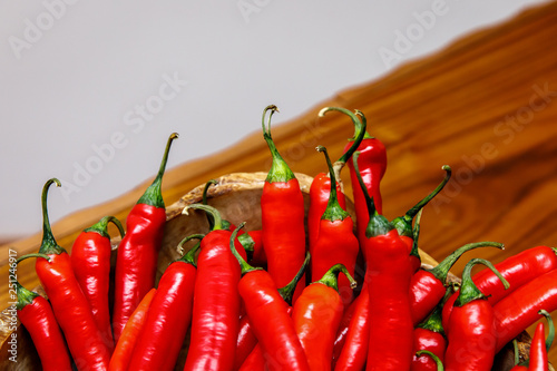 Red chili peppers on plate on wooden table