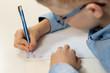 Dłonie chłopca trenującego naukę pisania. Pisanie liter długopisem w zeszycie w kratkę.