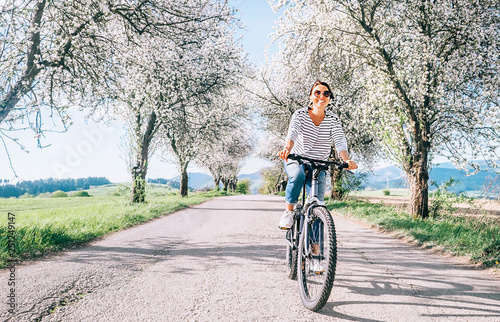 Fotografía  Happy smiling woman rides a bicycle on the country road under blossom trees