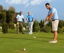 Golfer Putting Ball On Green