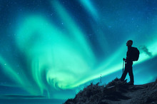 Aurora Borealis And Silhouette Of A Woman With Backpack At Night. Girl On The Hill, Starry Sky With Northern Lights. Sky With Stars And Polar Lights. Trekking. Landscape With Bright Aurora And People