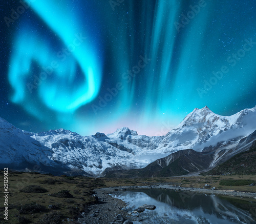 Poster Aurore polaire Aurora borealis over the snowy mountains, coast of the lake and reflection in water. Northern lights above snow covered rocks. Winter landscape with polar lights, lake. Starry sky with green aurora