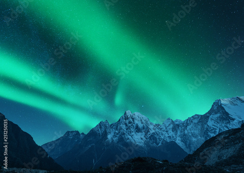 Poster Aurore polaire Aurora borealis above the snow covered mountain range in europe. Northern lights in winter. Night landscape with green polar lights and snowy mountains. Starry sky with aurora over the rocks. Space