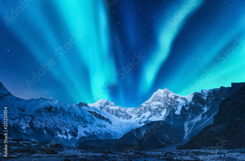 Wall Murals Northern lights Aurora borealis above the snow covered mountain range in europe. Northern lights in winter. Night landscape with green polar lights and snowy mountains. Starry sky with aurora over the rocks. Space