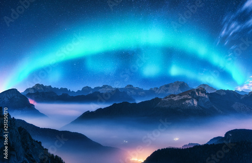 Poster Aurore polaire Aurora borealis above mountains in fog at night. Northern lights. Sky with stars with polar lights and high rocks. Beautiful landscape with aurora, city lights in low clouds, mountain ridge. Space