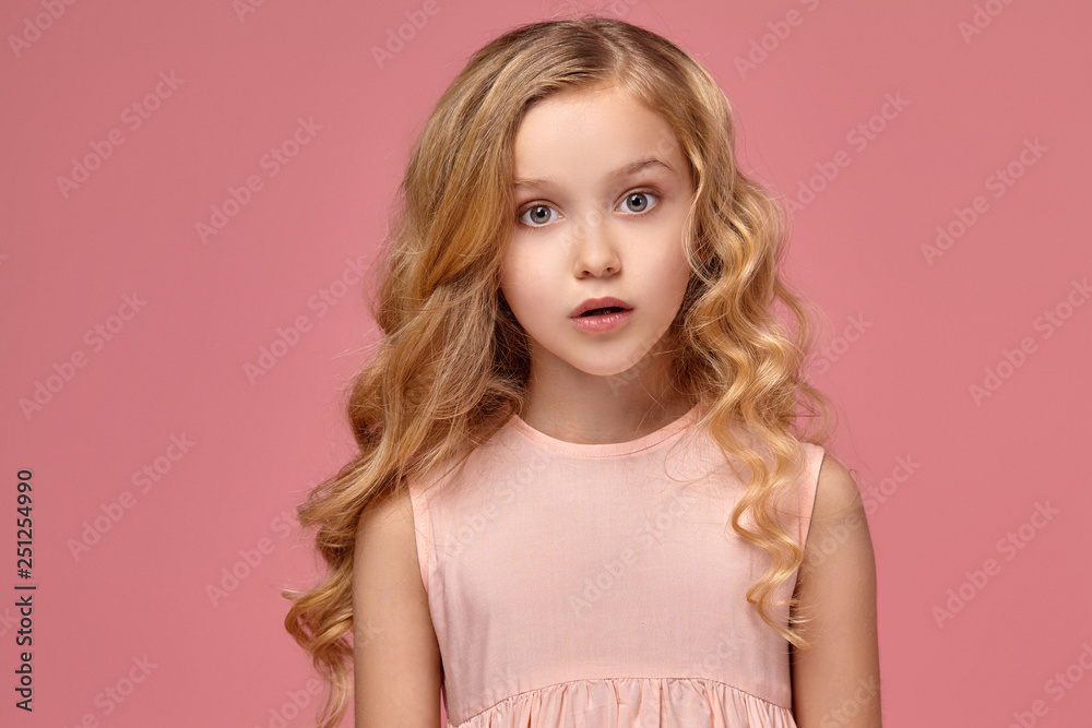 Fototapety, obrazy: Little girl with a blond curly hair, in a pink dress is posing for the camera