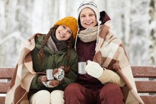 Waist Up Portrait Of Loving Young Couple Wrapped In Blanket Drinking Hot Cocoa Outdoors While Sitting On Bench Beautiful Winter Forest, Copy Space