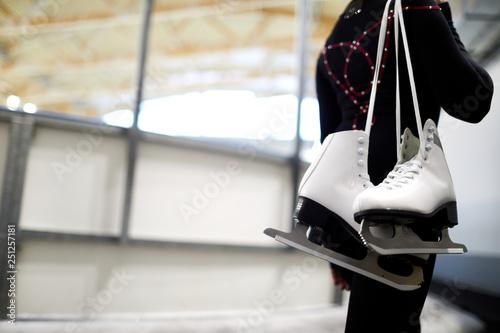Closeup of unrecognizable girl holding figure skates over shoulder leaving ice r Fototapeta