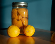 Two Lemons In Front Of A Canned Jar Of Peaches