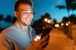 canvas print picture Man smiling looking at phone outside on city street at night texing online using smartphone. Young male face lit by screen light using mobile cellphone outdoors in the dark in summer.