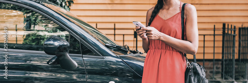 Obraz Car sharing rideshare mobile phone app woman using smartphone online to rent on travel holiday. Banner panorama. Technology device. - fototapety do salonu