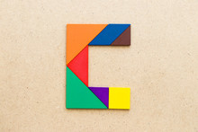 Tangram Puzzle In Alphabet Letter C Shape On Wood Background