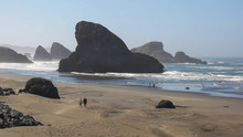 Tourists Walk Along The Sand Towards Sharkfin Rock On The Oregon Coast
