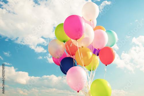 Obraz na plátně Colorful festive balloons over blue sky with a retro vintage instagram filter effect