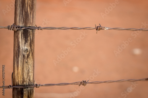 Fotografía  Rusty barb wire fence and old wood poles on Kalahari red sand farm