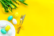 canvas print picture - Festive Easter table decorated with tulips. Tableware and painted eggs on yellow background top view copy space