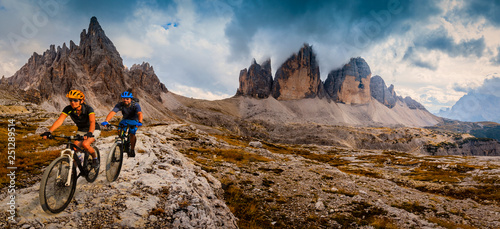 Foto auf Leinwand Rosa dunkel Cycling woman and man riding on bikes in Dolomites mountains andscape. Couple cycling MTB enduro trail track. Outdoor sport activity.