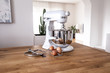 White kitchen machine and stand mixer on a wooden table in a bright design apartment