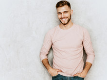 Portrait Of Handsome Smiling Hipster Lumbersexual Businessman Model Wearing Casual Summer Pink Clothes. Fashion Stylish Man Posing Against Gray Wall