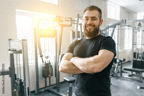 Portrait of smiling personal fitness trainer in gym, confident man with folded hands looking at camera Fototapet