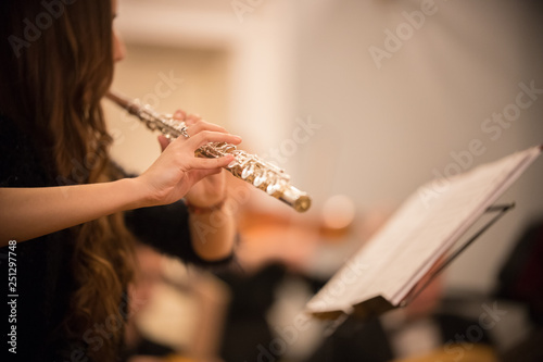 A young woman playing flute at the concert - 251297748