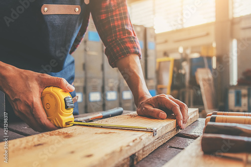 Obraz Carpenter working with equipment on wooden table in carpentry shop. woman works in a carpentry shop. - fototapety do salonu