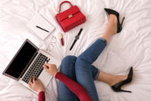 Young Businesswoman With Laptop Sitting On Bed