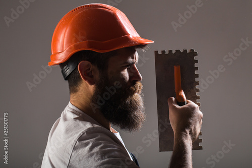 Tool, trowel, handyman, man builder. Mason tools, builder. Builders in hard hat, helmet. Bearded man worker, beard, building helmet, hard hat. Mason plastering concrete to build. Plastering tools.
