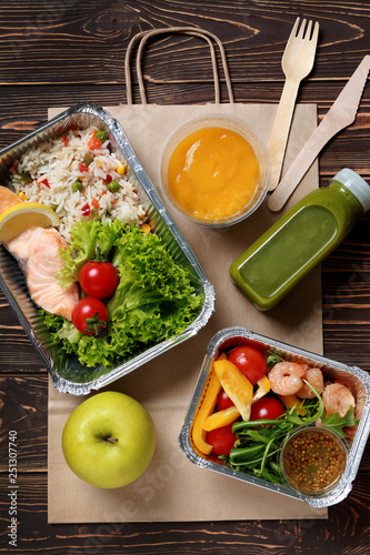 Containers with delicious food for delivery on wooden table