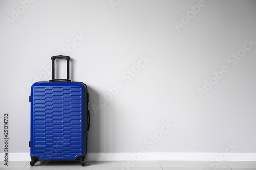 Poster Asia Country Packed suitcase near light wall