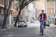 Young Asian Man Riding His Bike Along A City Street