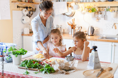 Fototapeta Family are cooking italian pizza together in cozy home kitchen. Cute kids with happy mother are preparing food or meal for dinner. Two girls are helping woman. Children chef concept. obraz